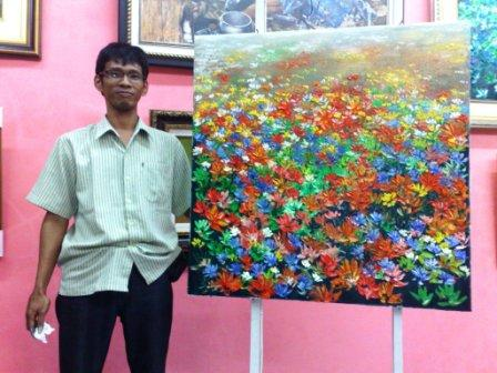 Darma posed after finishing a live painting demo in a gallery exhibition